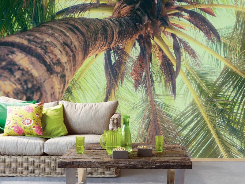 Akcentująca ściana z palmą tworzy w domu gorący wakacyjny klimat. Zrównoważ wnętrze, dodając spokojne tekstylia w podobnym stylu.