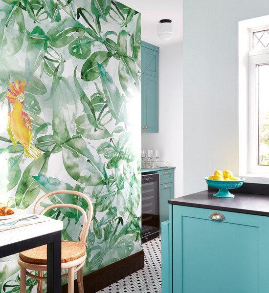 Akwarelowe liście z jaskrawym akcentem odnajdą się również w kuchni. Jaskrawe turkusowe szafki i białe ściany tworzą spójny tropikalny wystrój.