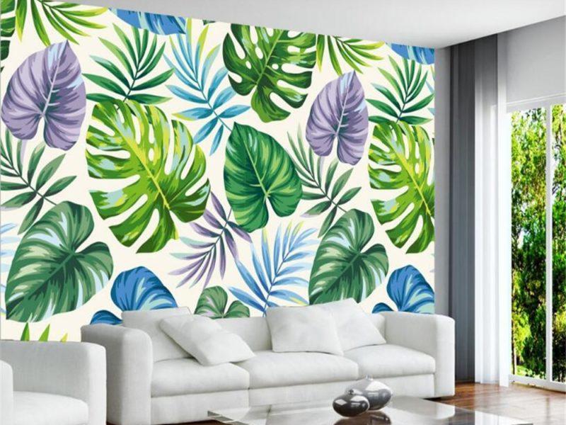 Kolorowe akcenty na liściastej tapecie pozwalają umieścić we wnętrzu barwne dodatki i tekstylia.