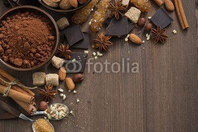 Fototapeta chocolate, cocoa, nuts and spices on wooden background, top view